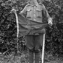 A soldier holding up a pennant flag