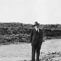Man standing on pebbles beside a river