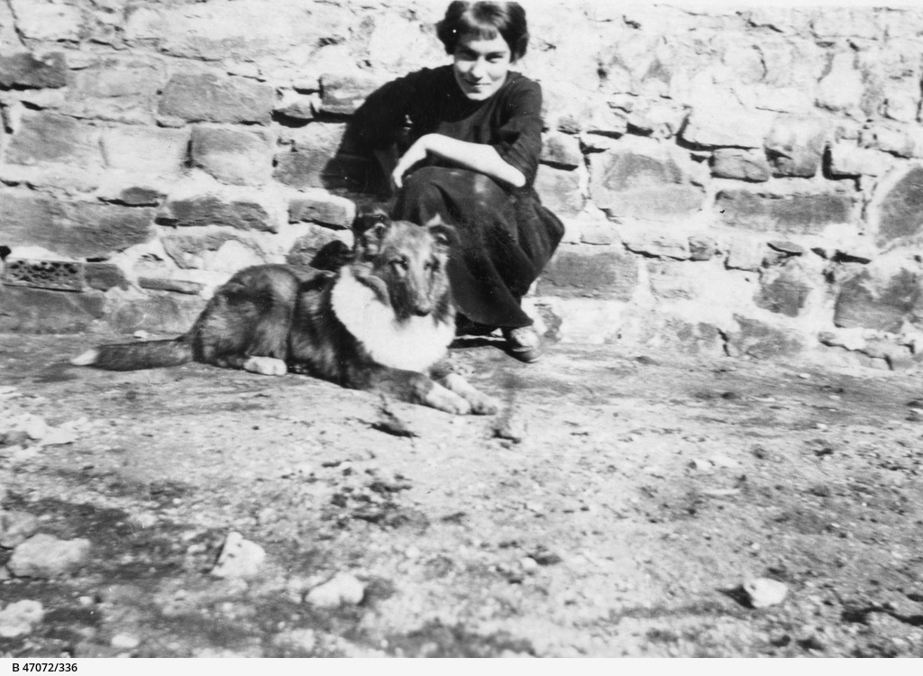 A dog sitting by a house wall with a young woman