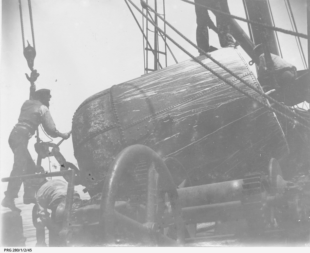 Seamen cleaning a ship's buoy lying on deck amongst machinery and rigging