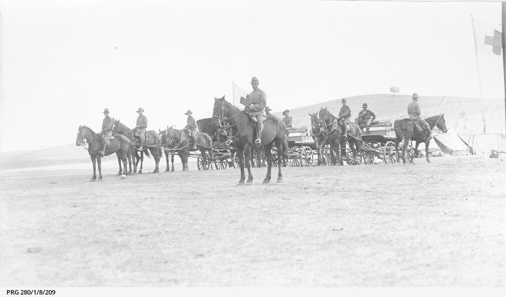 Mounted soldiers with horse drawn vehicles at an army camp during World War I