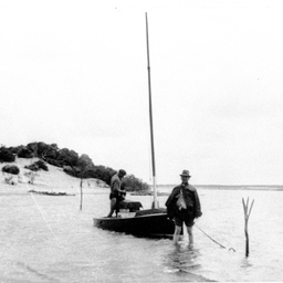 Two men with small boat at its anchorage at Nine Mile Point