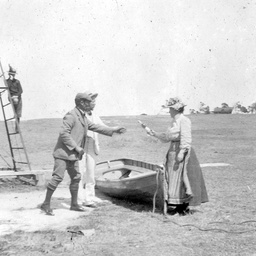 Holiday-makers by a beached rowing boat