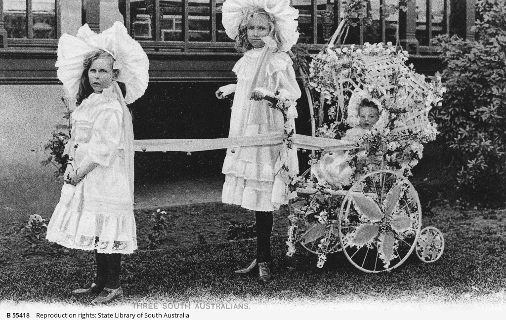 Two young girls with a young child in a decorated pram