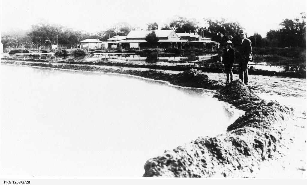 Two men inspecting the 1931 flood scene at Berri