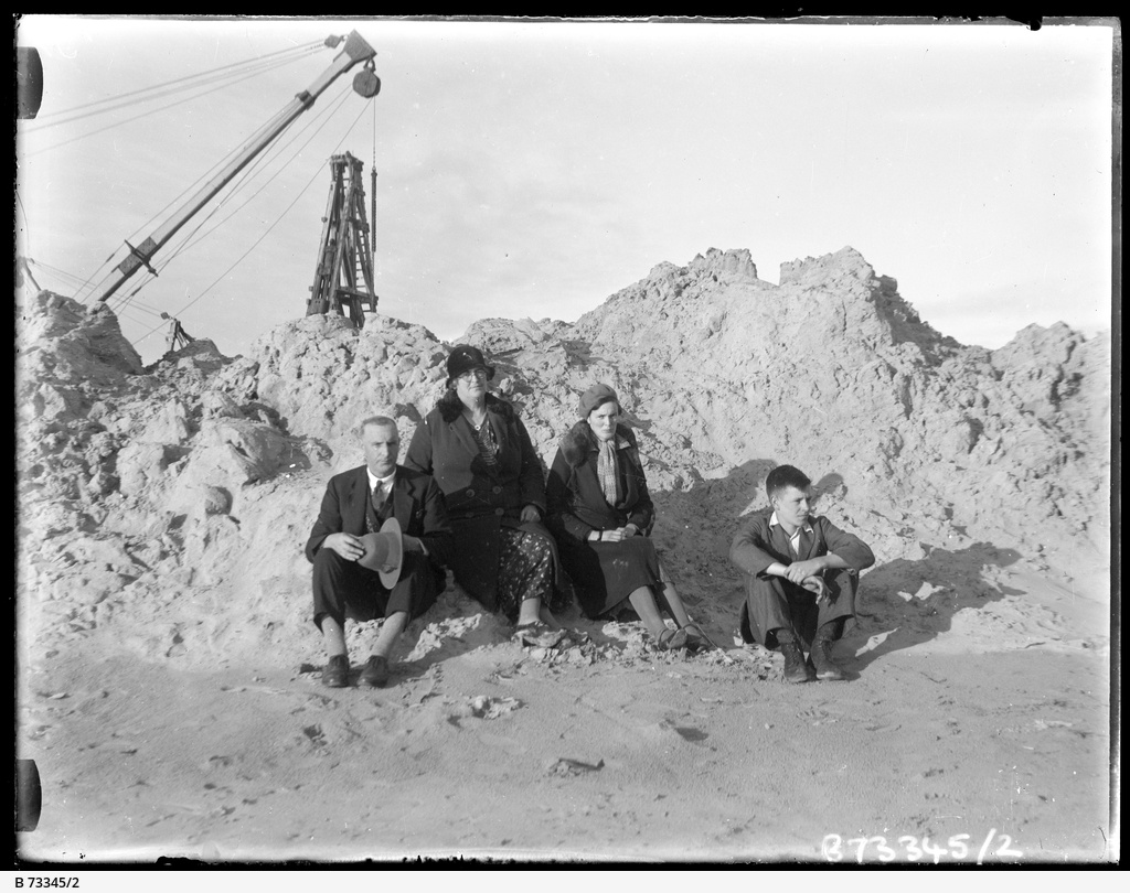 Group sitting on rubble.