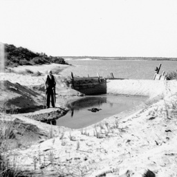 A man standing by a mooring basin or fishing dam at The Coorong