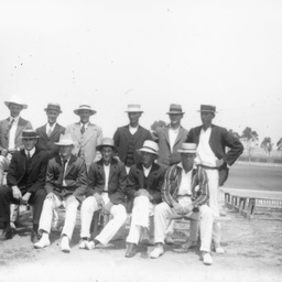 Group of young men posing beside an oval