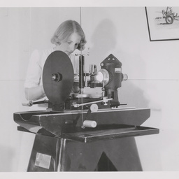 Woman working at an optical projector.