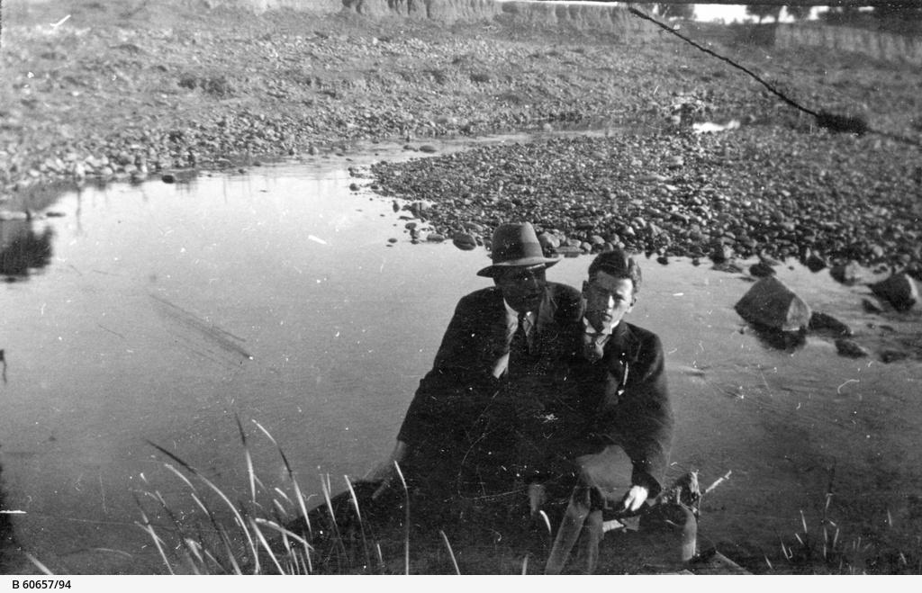 Two men sitting beside a waterhole