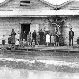 Echuca during a flood with a group including children on a verandah