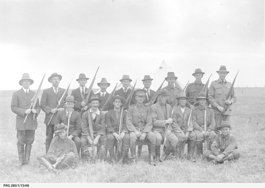 Group of fifteen men holding signalling flags with an army officer