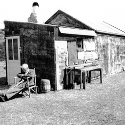 George Ross relaxing in a chair outside a shack at The Coorong