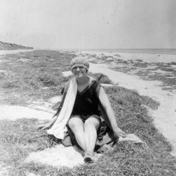 A woman wearing bathing costume sitting on sandhills