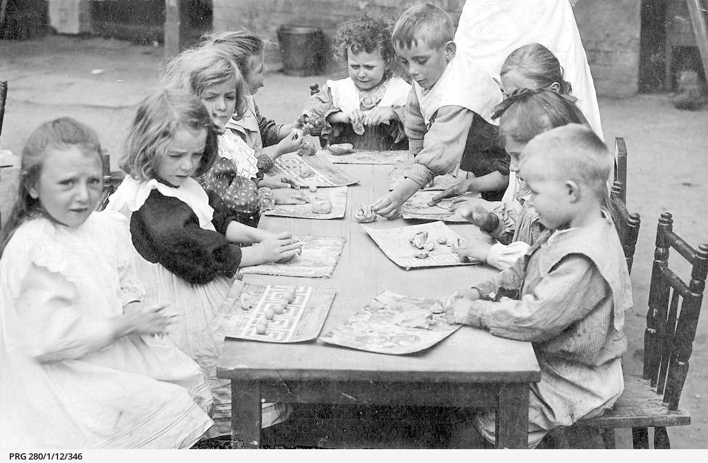 Kindergarten children playing with plasticine