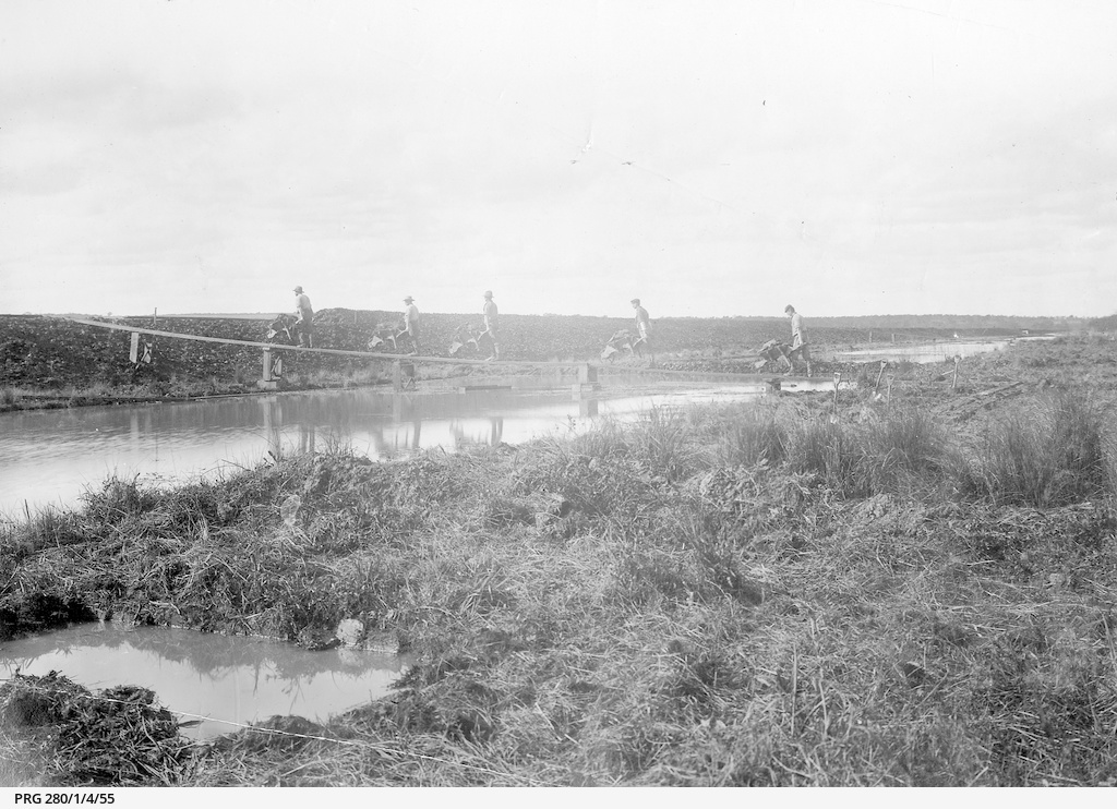 Four workmen pushing wheelbarrows on a temporary bridge across water to an area where an embankment is being formed near Port Adelaide