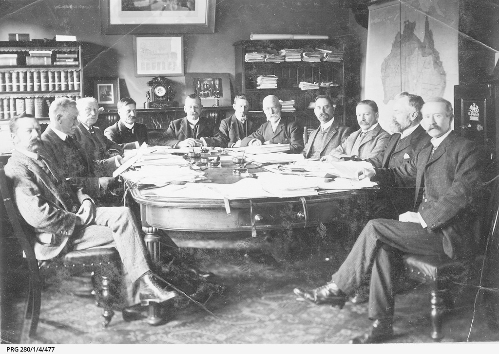 Eleven men sitting around a table in a large office