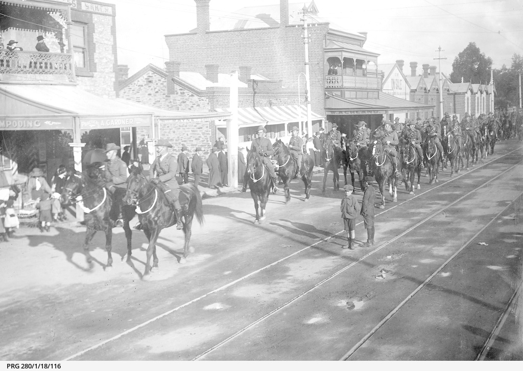Soldiers riding along an Adelaide street