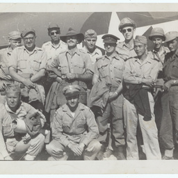 Group of servicemen standing in front of a plane