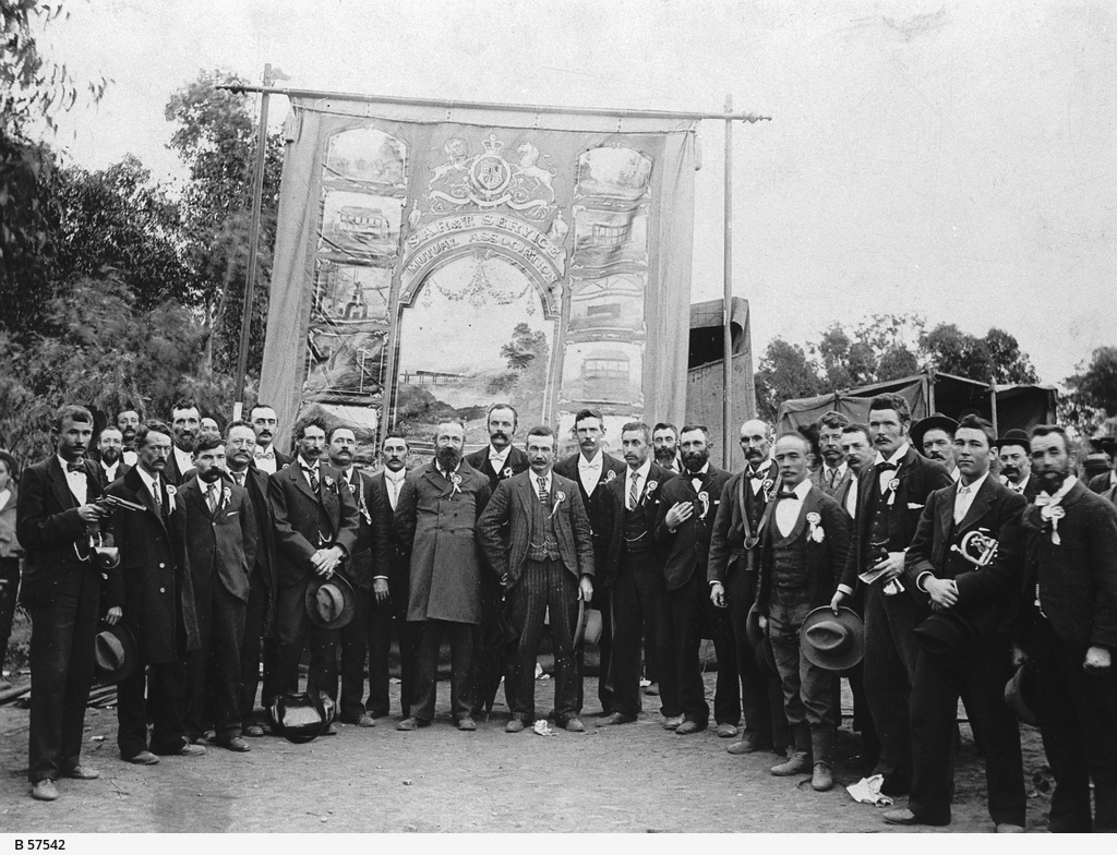 Men standing by a banner during celebrations at Quorn