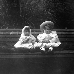 Two small Searcy family children sitting on a wooden garden seat