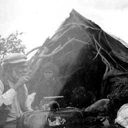 Aboriginal man and woman sitting outside their dwelling at Fowlers Bay