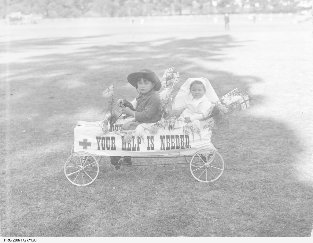 Two small children seated in a toy car