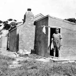 Man holding his fish catch at the doorway of a shack on The Coorong