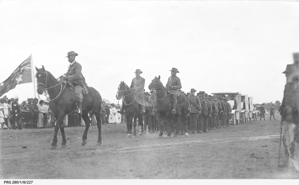 Mounted soldiers and vehicles parading past spectators during World War I