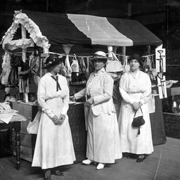 Three woman helping to sell goods from a stall in aid of the war effort during World War I