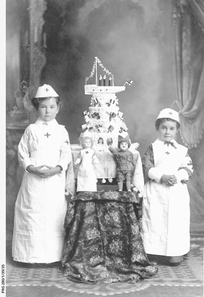 Two children dressed as Red Cross nurses