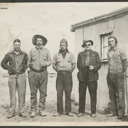 Five men outside a galvanised iron building