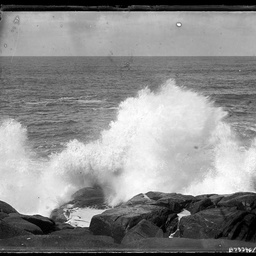 Wave crashing over rocks.