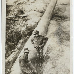Two soldiers standing by a 50 foot gun