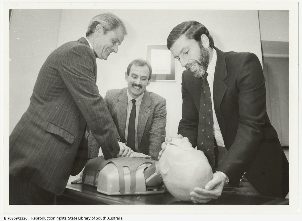 West Beach Surf Lifesaving Club member Greg Mutton explains use of the ambumannequin to West Lakes Mall manager Patrick Jordan and Delfin Group administrator/secretary David Knowler. 13 July 1988.