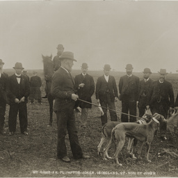 Group of men with greyhounds
