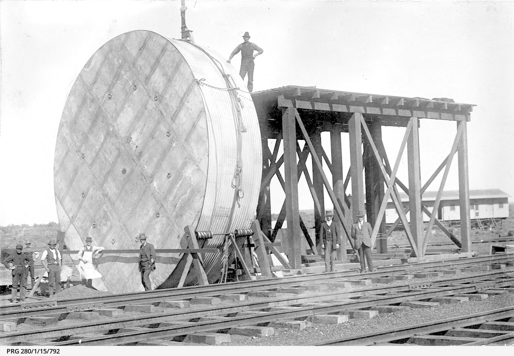 Men standing with a large water tank to be erected on a tall