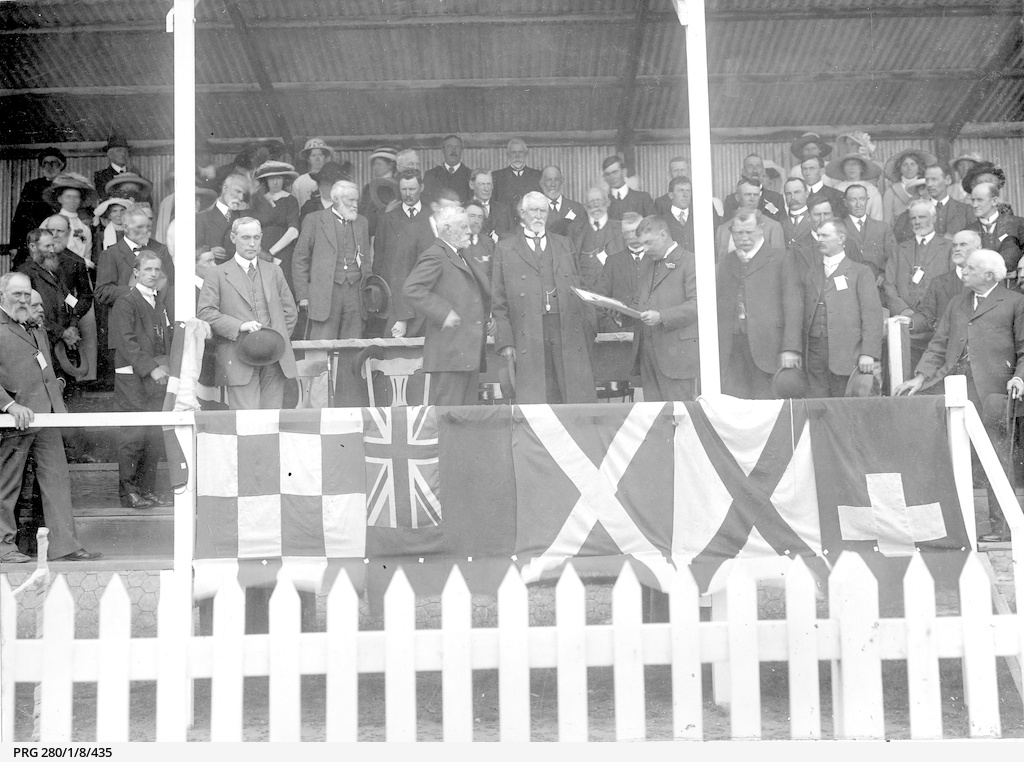 Sir Day Bosanquet, Governor of South Australia, listening to an oration read to an audience in a grandstand at Strathalbyn Show