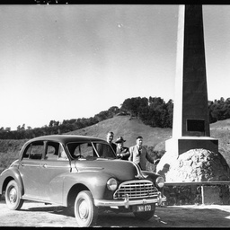Three men with car at a monument