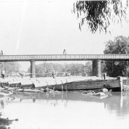 Outrigger barge loaded across with huge logs at Echuca