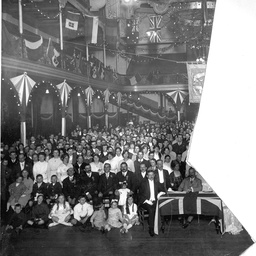 Part of an audience seated in a large hall