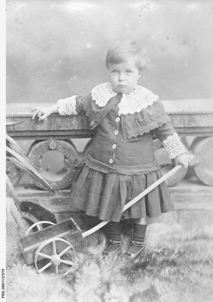 Studio view of a small boy wearing a lace trimmed dress and holding a toy cart