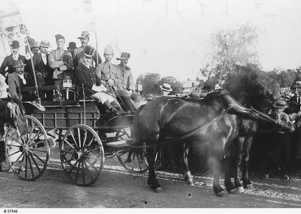 Men sitting on a horse drawn carriage