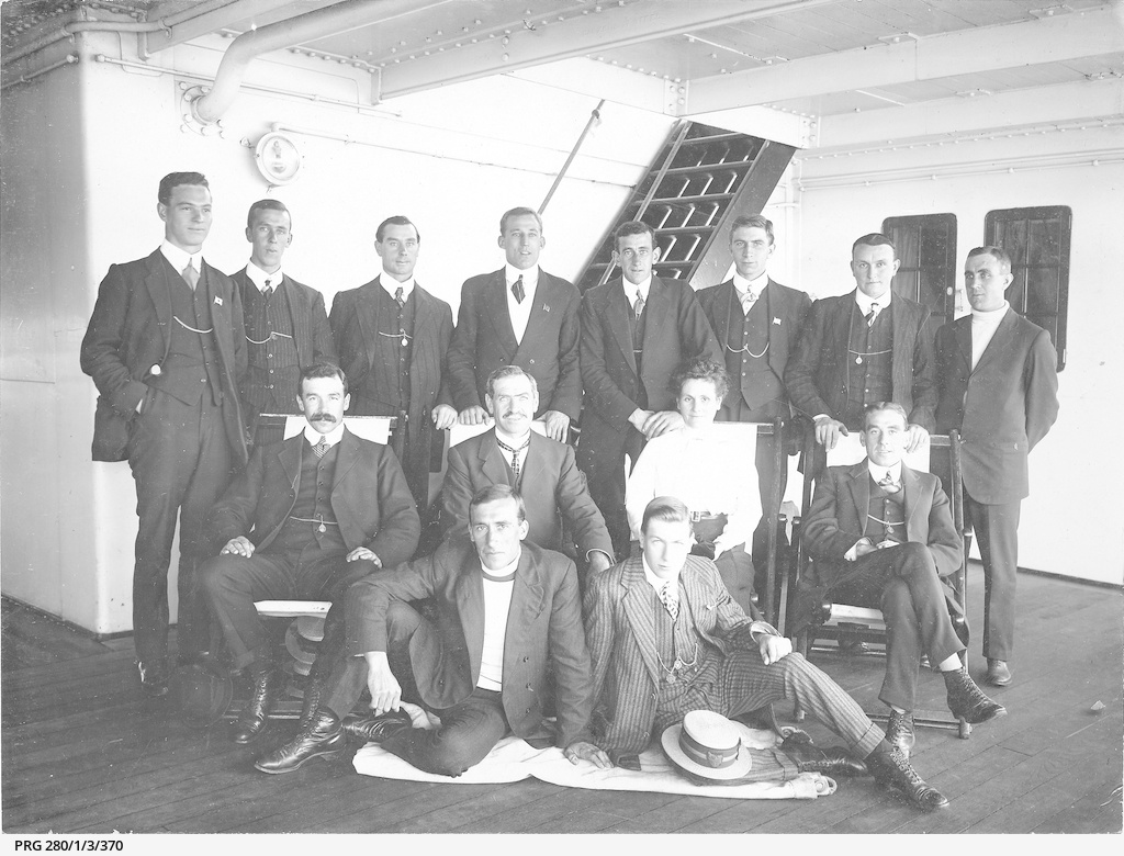 Thirteen men and one woman seated and standing in a formal group on board a ship