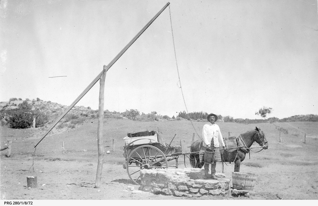 A man collecting water from an old well, Port Noarlunga