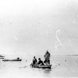 Several men in small rowboats fishing at Narrung