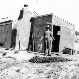 A man with a rifle outide a shack at Nine Mile Point