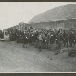Townspeople gathered by a wall.