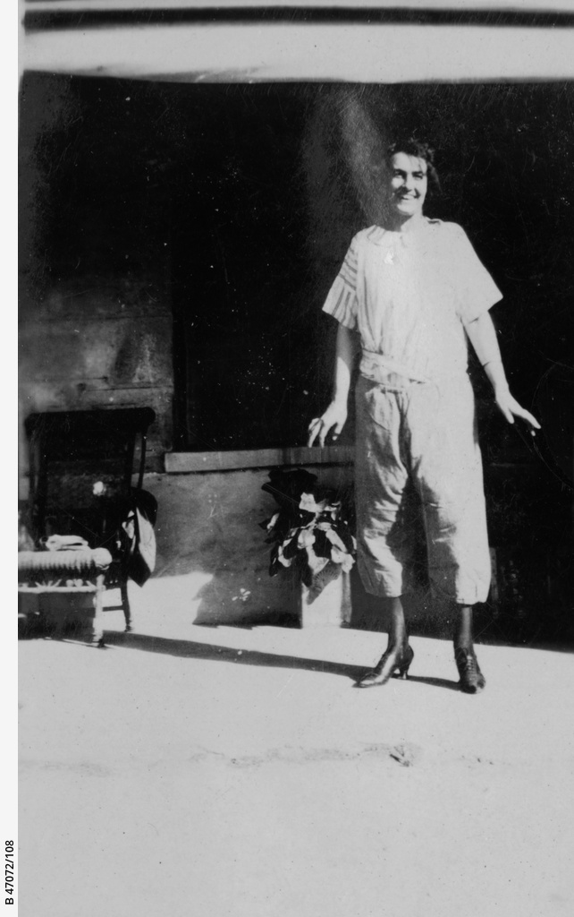 A woman wearing trousers standing on a verandah