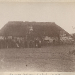 Group of men, women and children at a mission station on the Finke River